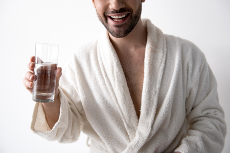 Optimistic young bristled man in bathrobe is standing with fresh water. He is smiling. Isolated background Stock Photo
