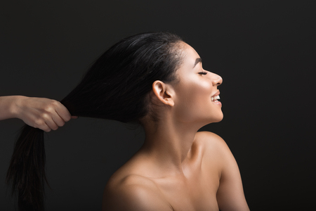 Profile of woman being positive. Someone pulling her by hair. Isolated on black background