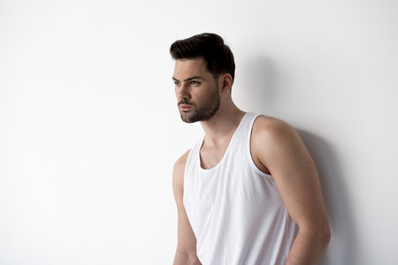 Young attractive man is standing against light wall while looking aside thoughtfully. Copy space in the left side
