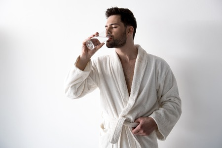 Cute stylish bristled guy in white bathrobe is standing and enjoying cold beverage. Isolated on light background 스톡 콘텐츠