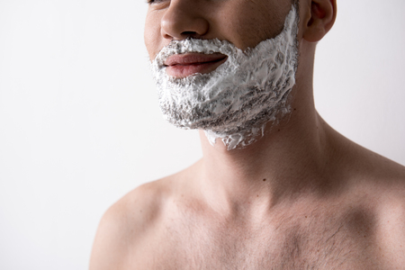 Close up of chin of young positive topless man is standing with shaving foam on his face and smiling. Skin care concept. Isolated on light background