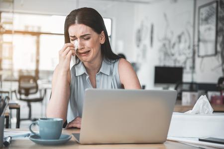Porträt der weinenden Dame, die Tränen mit Seidenpapier abwischt, während sie mit Gerät am Schreibtisch steht. Trauriges Mitarbeiterkonzept