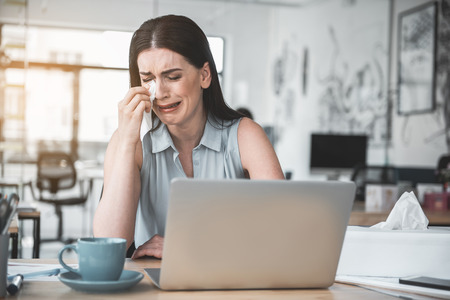 Portrait of crying lady wiping tears away tears with tissue paper while locating at desk with gadget. Sad employee concept