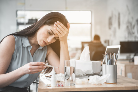 Portrait of unhappy female checking temperature while locating at table in office. Sick employer concept