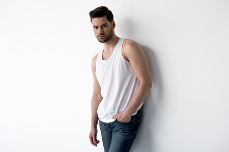 Portrait of serious young stylish man is leaning on light wall. He is looking at camera confidently while holding hand in pocket of his jeans