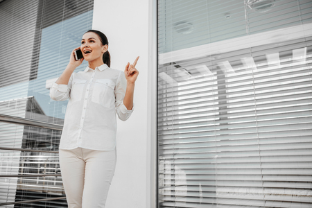 Low angle of satisfied businesswoman standing on porch and speaking by phone. She holding finger up. Copy space in right side
