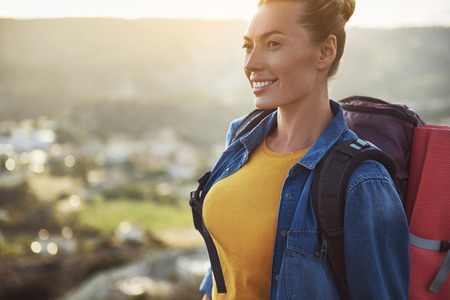 Portrait of female person with rucksack on her back looking aside and smiling. Focus on girl. Copy space in left side