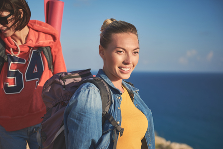 Happy females with rucksacks standing on the top of hill and staring at shore Stock Photo