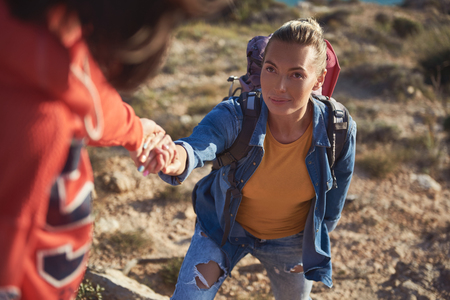 Portrait of calm woman going uphill. Friend helping her and giving hand Stock Photo