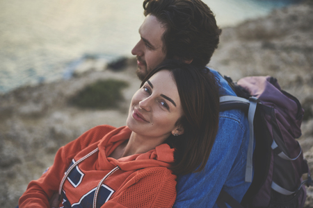 I am really happy. Portrait of glad young woman looking at camera and smiling. Man is hugging her with love while viewing sea landscape Foto de archivo - 101552134