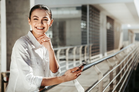 Portrait of cheerful female person holding smartphone while standing on terrace. She is looking at camera and smiling. Copy space in right side