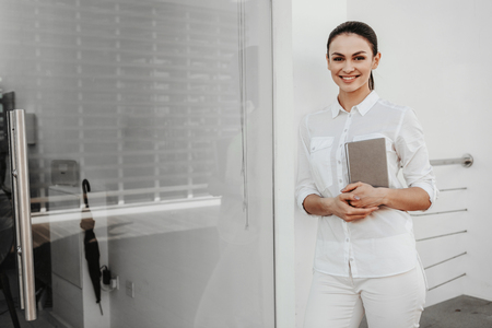 Portrait of young lady standing in workplace and looking at camera with beautiful smile. Notepad is in hands. Copy space in left side
