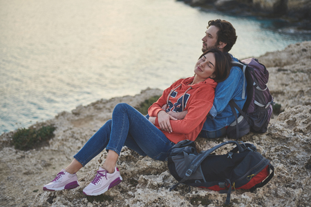 Listening to ocean sounds. Pleased young woman enjoying hug of her boyfriend while sitting on the rock near water. Her eyes are closed with pleasure Stock Photo