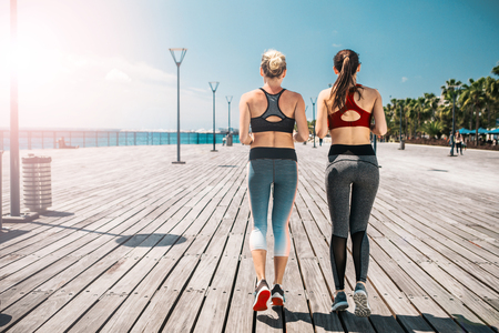 Full length of fit two young women jogging near the sea together. Focus on their back 写真素材