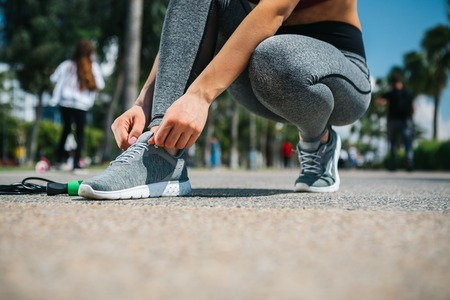 Low angle close up of female legs. Active woman is tying laces on her sneakers while kneeling on the road