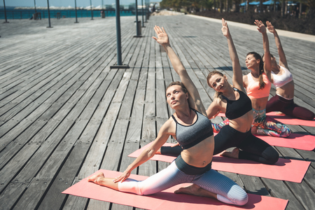 Full length side view serene ladies stretching bodies while raising hand up on rugs outdoor. Concentrated female doing physical drill concept Stock Photo