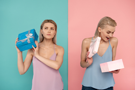 Waist up of two attractive joyful women opening colorful boxes. blue and pink background