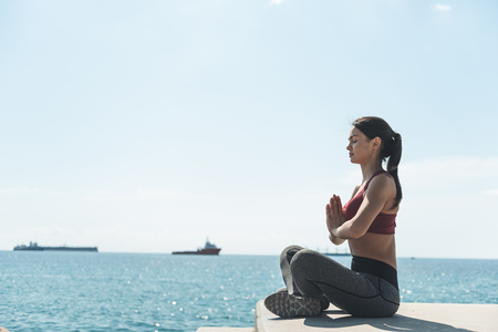 Full length side view orderly lady sitting in lotus posture opposite sea. Peace of mind concept