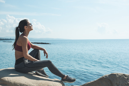 Full length side view calm woman enjoying sea air while sitting on stone. Copy space