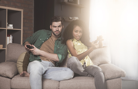 I win. Portrait of young couple is playing video games at home with controller. They are looking at camera with concentration while sitting on cozy sofa