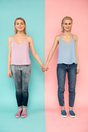 Full length portrait of two good looking ladies standing, holding hands and looking at camera with happiness Stock Photo - 101667047