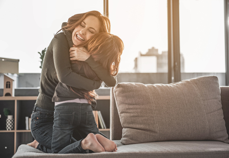 I missed you. Full length portrait of excited mother and her small daughter embracing tightly at home. Woman is holding her kid with delight and joy. Copy space in right side