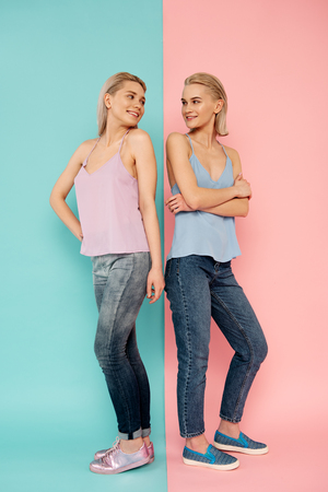 Full length portrait of two sisters standing back to back on blue and pink background. They looking each other with joy