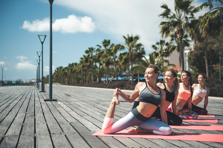 Full length portrait of cheerful young women raising legs upwards while lying on mat outdoor. Happy ladies making exercise concept