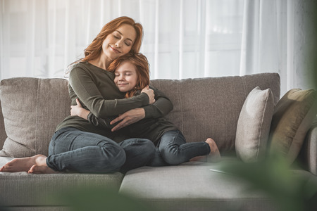 My dearest. Full length portrait of mother and her child hugging each other and sitting on couch at home. They are smiling, calm and happy 写真素材