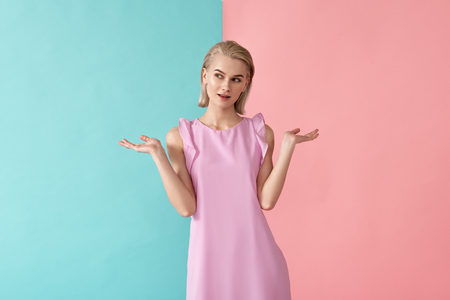 Portrait of blonde girl standing in summer clothing. Isolated on blue and pink background