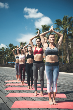 Full length portrait of happy women doing gymnastic exercise at in nature. Happy comrades during training concept