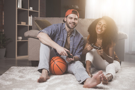 Full length portrait of cheerful young delighted couple is playing games on console together. They are sitting on floor while looking at camera with joy