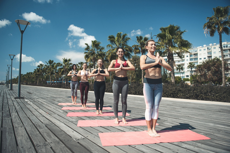 Full length portrait of cheerful women practicing yoga in nature. Happy comrades during training concept