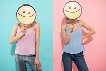 Waist up of two contented young ladies in t shirts and jeans standing on blue and pink background