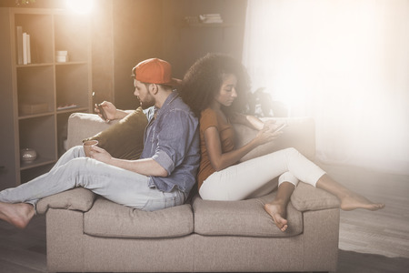 Side view of young couple is sitting at home on cozy sofa turned back to each other and holding mobile phones. They are looking at screen of gadgets with concentration surrounded by sunlight