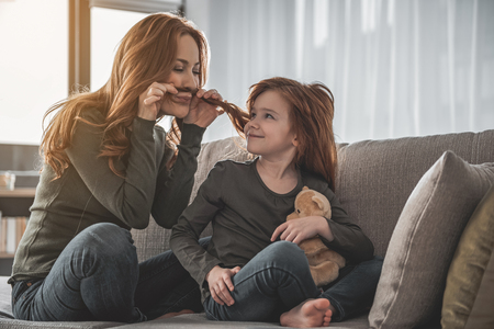 Full length portrait of high-spirited, energized woman with her small daughter playing on sofa. Mother is putting her child curls to her face as if mustache Stock Photo