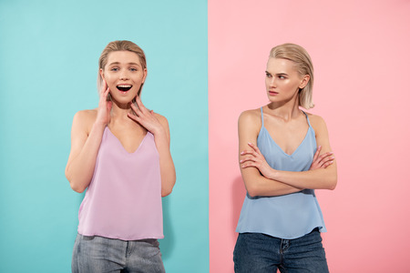 Waist up portrait of beautiful lady in pink expressing delight, other girl in blue shirt is looking at her with envy