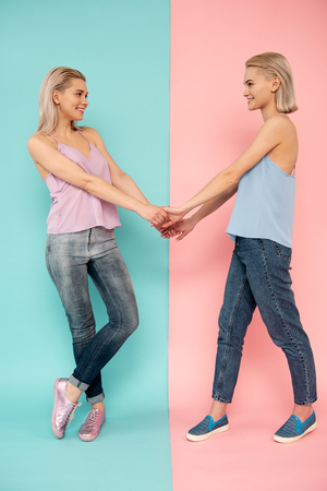 Full length of two cheerful blonde girls posing on blue and pink background, they are holding hands and looking at each other with smile Stock Photo - 101803852