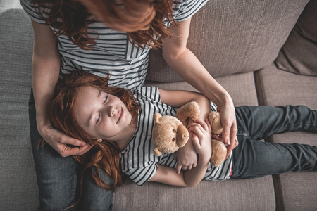 Top view of small kid lying peacefully on sofa holding teddy bear with her mom. Pleased woman is stroking her daughter hair Stock Photo