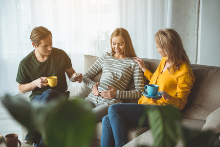 We are waiting for you together. Happy pregnant woman is touching her belly and smiling. Surrogate parents are sitting near and drinking hot beverage