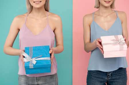 Two young female people standing with cute boxes and smiling. blue and pink background