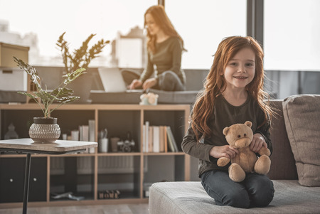 Play with me. Full length portrait of happy, red-haired girl holding her teddy bear and waiting for her mother to come closer. Woman on the background is using her laptop