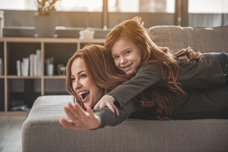 Up. Waist up portrait of laughing red-haired woman and smiling daughter playing together. Small girl is lying on her mother and holding hands as if being bird