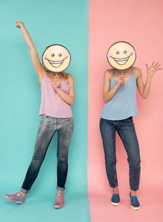 Full length of two jokey ladies covering faces with laughing smileys, standing on blue and pink background