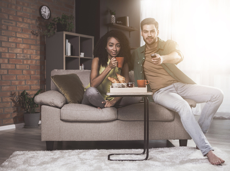 Full length portrait of young pleasant couple is sitting together on cozy sofa while looking at camera with slight smile. Girl is drinking tea while guy is holding tv console. They are having lunch