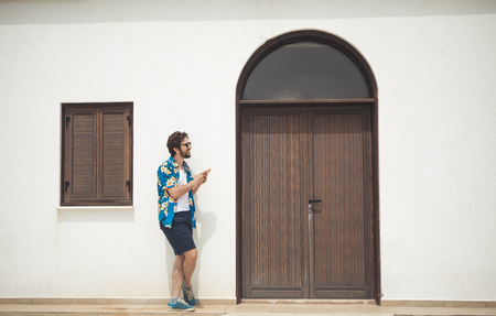 Did I find the right place. Joyful young man is looking at the door of someone house with anticipation. He is using smartphone navigator and laughing.  Summer traveling concept
