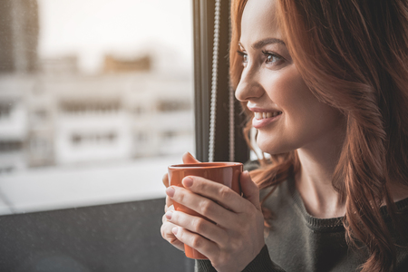 Sweet home. Close up of serene smiling girl with dreamy look. She is sitting near the window with a cup of her favourite drink enjoying her time. Copy space in left side Stock Photo