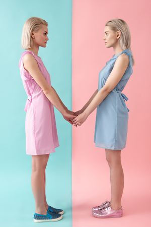 Side view profile of serious women standing in dresses, holding hands and looking at each other