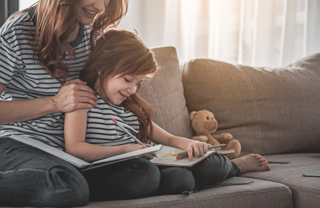 Family harmony. Portrait of smiling kid sitting on sofa with her mom holding her shoulders. Red-haired woman is watching her daughter with content. Pencils are scattered on sofa beside them Stock Photo