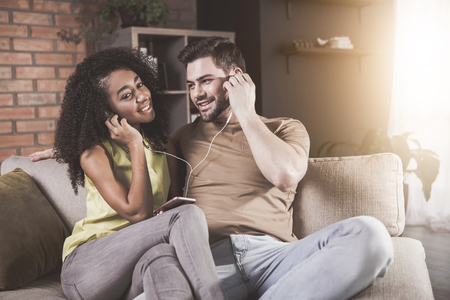 Having fun together. Portrait of delighted young boyfriend and girlfriend are sitting on sofa and listening to music on smartphone. They are using headphones. Man is looking at girl with adoration